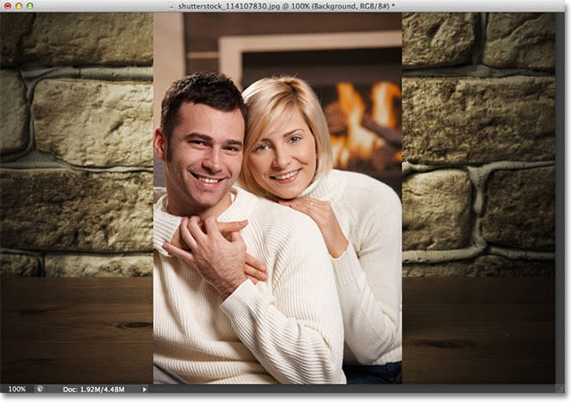 Young couple hugging on sofa in front of fireplace. Image licensed from Shutterstock by Photoshop Essentials.com