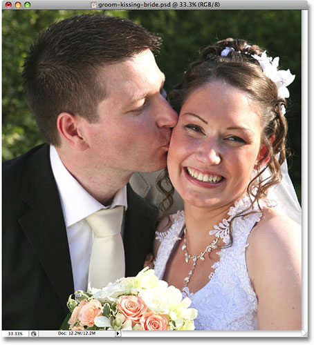 A wedding photo of a groom kissing the smiling bride. Image copyright © 2008 Photoshop Essentials.com
